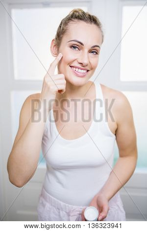 Young woman applying cream on face in bathroom at home
