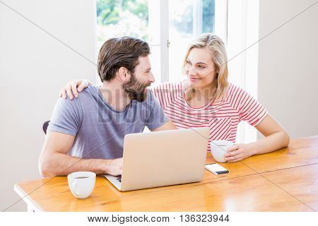Couple looking at each other while using laptop and holding a coffee cup at table