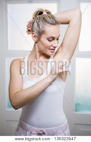 Young woman applying powder on her underarms in bathroom