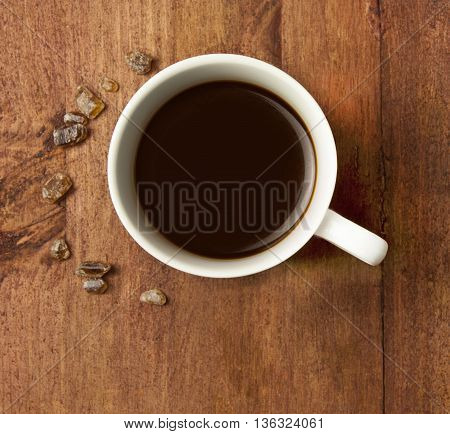 A cup of black coffee in a white cup with cane sugar on a dark wooden texture shot from above with copyspace