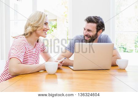 Couple looking at each other while using laptop at home