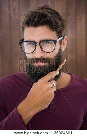 Hipster man doing his beard at work
