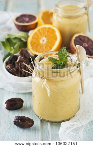 Healthy and fresh orange and date fruit smoothie on blue wooden table. Selective focus.