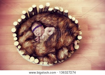 newborn baby sleeps in a wooden cradle of the primitive red fur