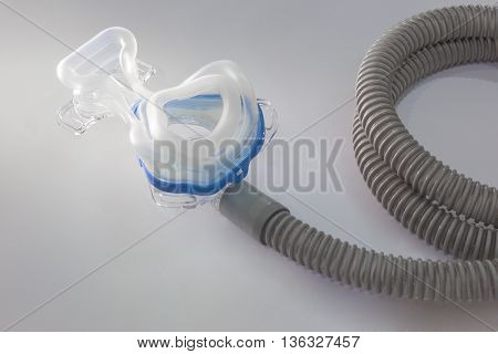 Sleep apnea CPAP mask and hose on light background to use with CPAP machine for people with sleep apnea or sleep disorder lighting emphasizes on mask