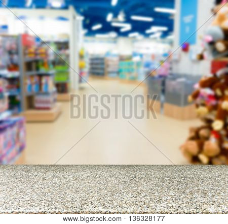 Marble board empty table in front of blurred background. Perspective marble table over blur in kids toy store. Mock up for display or montage your product.