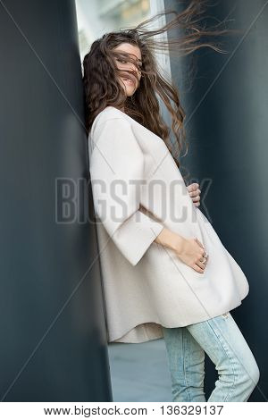 Attractive girl with windblown hair leans on the column outdoors. She wears a cream coat and light ripped jeans. She looks into the camera and holds her hands on the coat. She has rings on the right hand. Photographed from the side. Vertical.