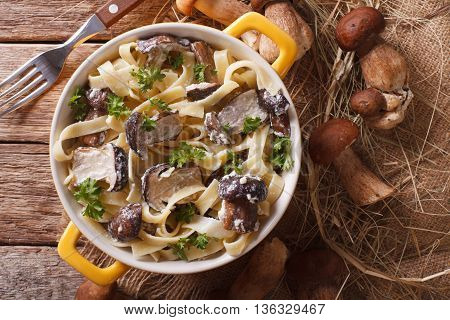 Fettuccine Pasta With Porcini And Cream Sauce Close-up In A Yellow Pot. Horizontal Top View