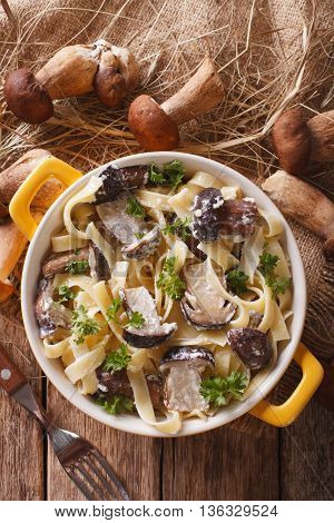 Fettuccine Pasta With Porcini And Cream Sauce Close-up In A Yellow Pot. Vertical Top View