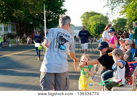 SOUTH ST. PAUL, MINNESOTA - JUNE 24, 2016: Supporter of local candidate for State Senate Dan Schoen hands out information at annual South St. Paul Kaposia Days Grande Parade on June 24.