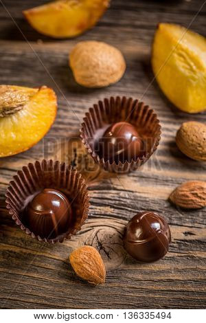 Chocolate bonbon with almond and apricot on wooden background