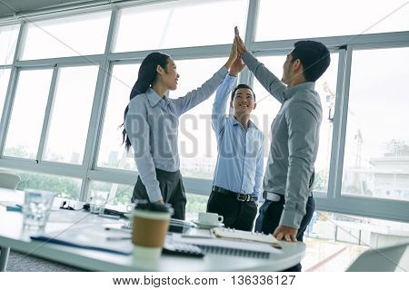Cheerful young business colleagues giving high five