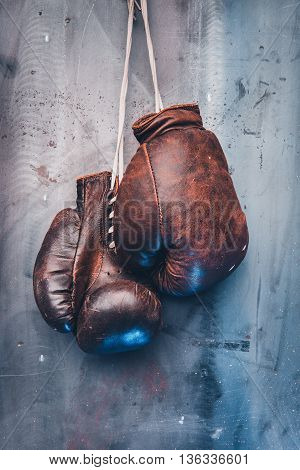 pair of brown vintage boxing gloves hanging on a metal wall