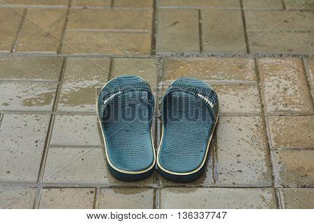 green wet summer bedroom slippers on conrcete under rain