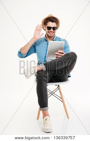 Smiling casual handsome man sitting on the chair and talking using tablet computer isolated on the white background