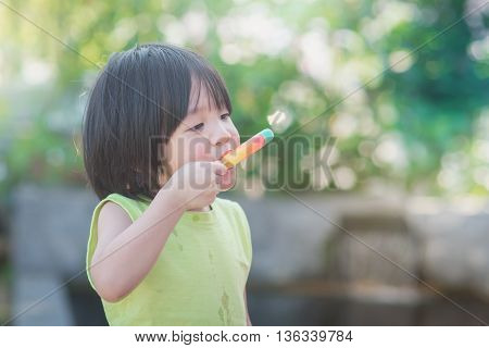 Cute Asian child eating an ice cream outdoors
