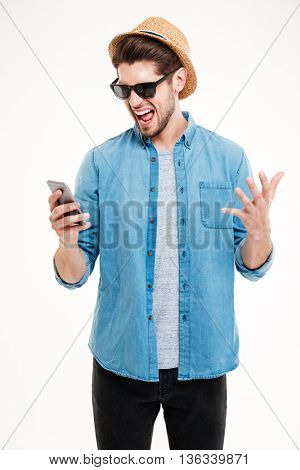 Close-up portrait of angry young man shouting at his smart phone isolated on white background