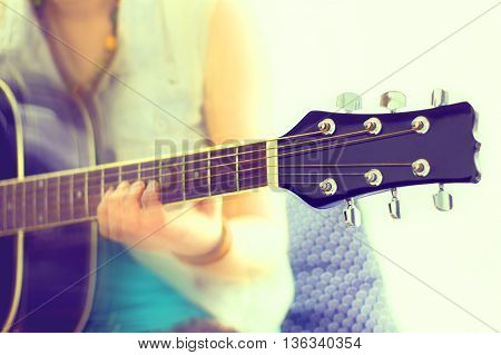 close up shot of strings and guitarist hands playing guitar over black - shallow DOF with focus on guitar colorized