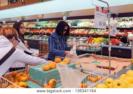 NAPERVILLE, ILLINOIS / UNITED STATES - NOVEMBER 3, 2015: People shop for fresh persimmons at the Super H Mart Korean supermarket in Naperville.