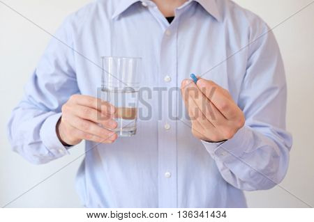 Man taking a pill with water in a glass