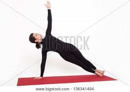 Beautiful athletic girl in black suit doing yoga. vasishthasana asana sage pose. Isolated on white background.