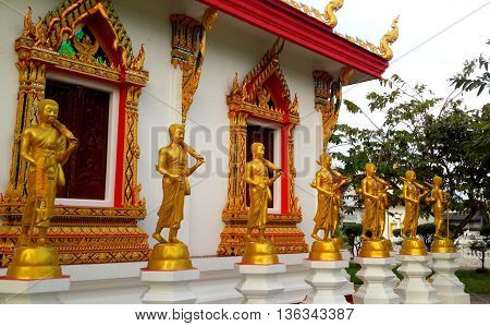 golden Buddha statues surrounding building at Buddhist temple, Songkhla, Thailand