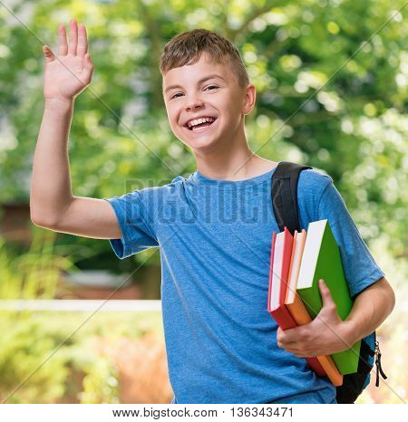 Smiling teen boy stretching his right hand up for greeting. Schoolboy with books posing outdoors.