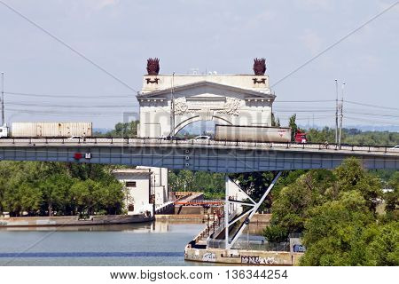 VOLGOGRAD - JUNE 29: Trucks over the bridge through the Volga-don canal in the background the arch of the first gateway. June 29 2016 in Volgograd Russia.