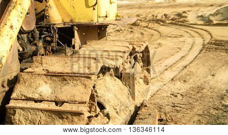 Big bulldozer performs work in the sand quarry