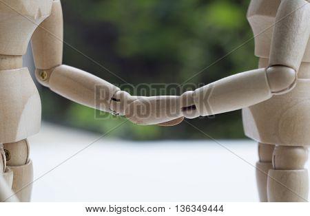 dummy wood man acting business shake hand