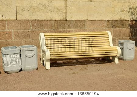 House wall is a bench.Tired can sit down and relax.Next to litter bins.