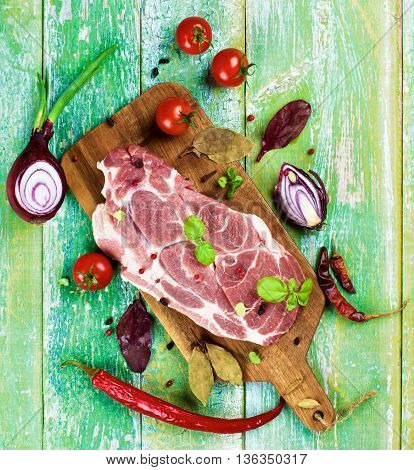 Perfect Raw Pork Neck with Spices Ripe Tomatoes Halves of Red Onion Herbs and Fresh Basil Leaves closeup on Wooden Cutting Board. Top View