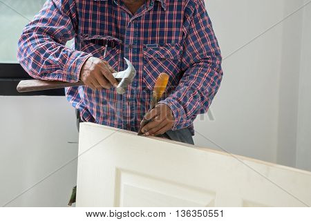 Carpenter Installer With Hammer And Chisel At Wood Door