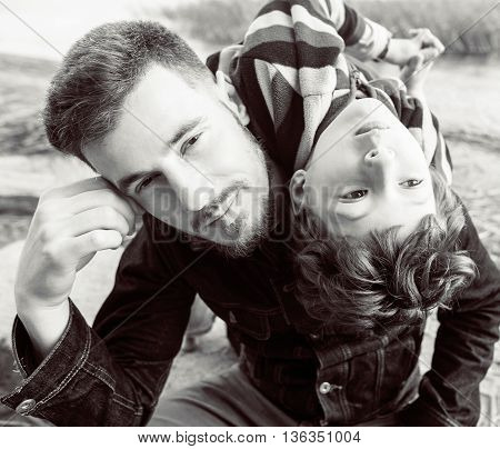 Young father hipster with a beard and his little son on the lake shore. Talking, teaching, having fun happy time. Lifestyle people concept. Black amp White
