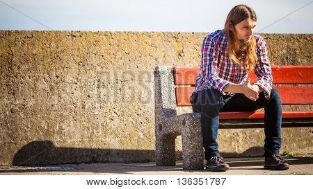 Man long hair alone on bench lost in thought is concerned and stressed about events in his life. Unemployment depression concept