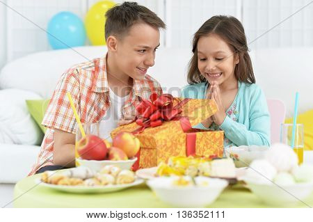 Happy  children  with cake and gift at birthday party