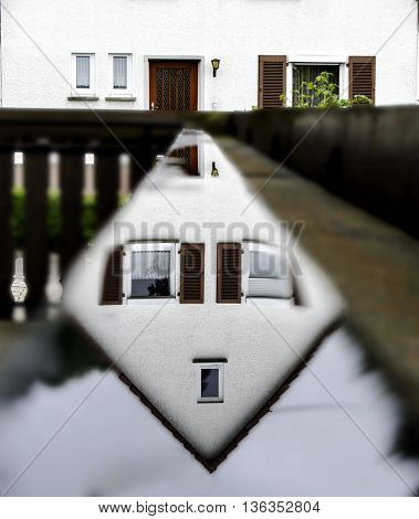 Reflection of the upper part of the house in the rain water on a wooden railing