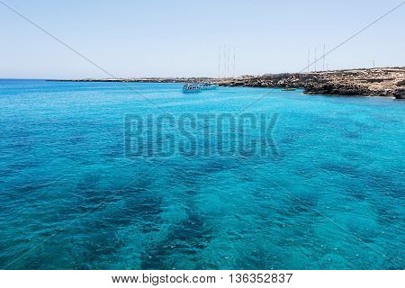 Blue lagoon with boats and swimming people in protaras paralimni immaculate water blue sea and rocks cyprus island