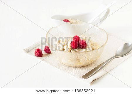 Oatmeal Porridge With Raspberries On Bright Wooden Table