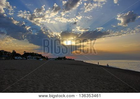 beautiful dawn, the sunrise from behind the clouds on the beach, the sand, the sea, the fishermen with fishing rods