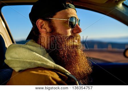 bearded guy driving car at sunset