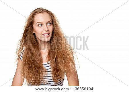 Excited teen girl looking to the side in amazement. Surprised happy young woman looking sideways in excitement.