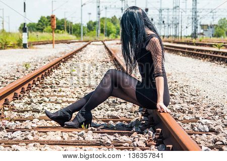 Young beautiful girl in black dress and nylons sitting on rail tracks, cargo wagons in background, face covered with hair, anonymous