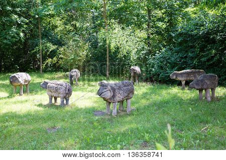 wooden sheep figures on sunny meadow grassland