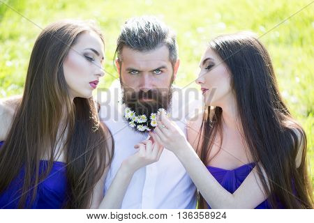 handsome man in white shirt with dandelion flowers in beard with two young pretty women in violet dresses on green grass sunny day outdoor