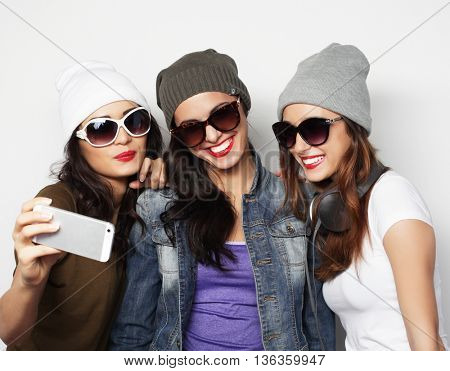 friendship, people and technology concept - three happy teenage girls with smartphone taking selfie