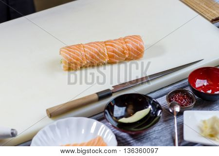 Sushi roll on cooking board. Knife lying beside sushi. Traditional uramaki rolls with salmon. Dish made of fresh ingredients.
