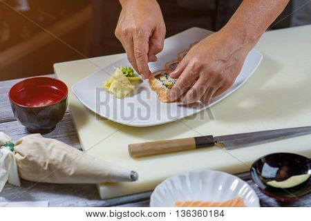 Male hands touch sushi rolls. Sushi and wasabi on plate. New recipe of japanese meal. Uramaki rolls with fish.