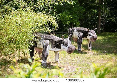 wooden milk cow figures on sunny meadow grassland