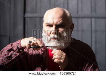 Old Man Cutting Beard With Scissors